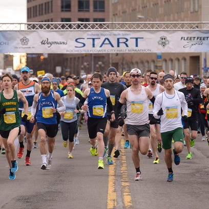 Racers begin the Flower City Half Marathon on the Broad