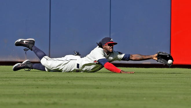 Atlanta Braves center fielder Cameron Maybin (25) nearly catches a fly ball from New York Mets Juan Lagares (12) as he dives for it during the ninth inning of a baseball game Sunday in Atlanta.