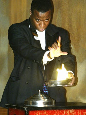 """""""Glamente"""" the magician performs a fire-to-live dove trick at Illusions Restaurant in Carmel before it closed in 2003."""