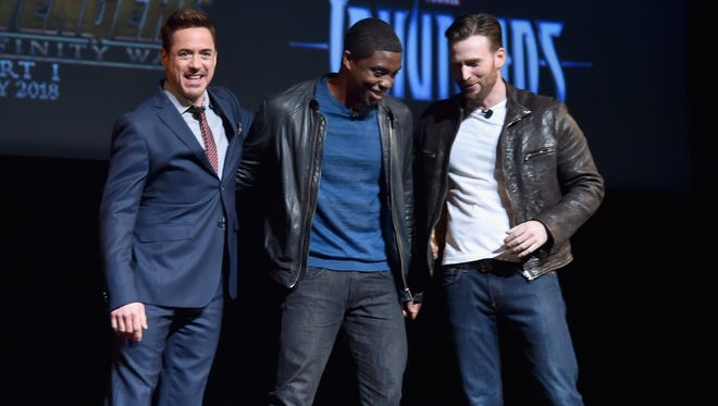 """Robert Downey Jr. (""""Iron Man""""), Chadwick Boseman (""""Black Panther"""") and Chris Evans (""""Captain American"""") get together onstage during a Marvel Studios fan event Tuesday in Los Angeles."""