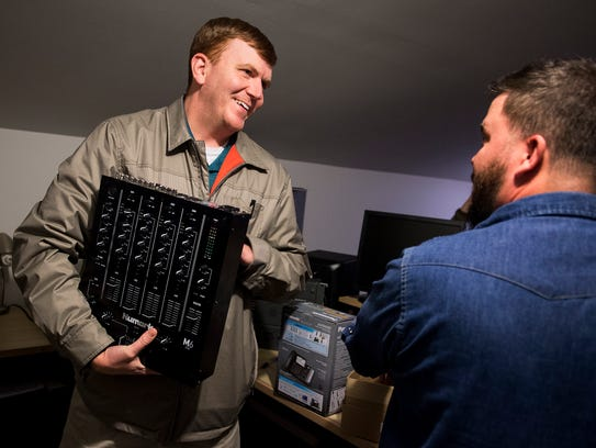 Jonathan Grigsby, left, unboxes new equipment at the