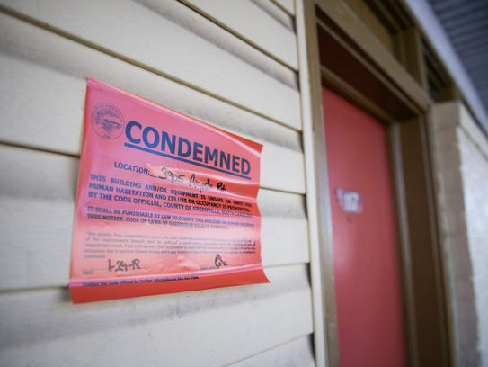 A condemned sign hangs outside of a room at the Economy