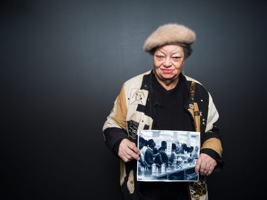 Ruth Ann Butler holds a photograph from one of the