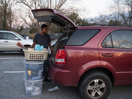 Thomas Smith packs a car with his belongings from Nicholtown