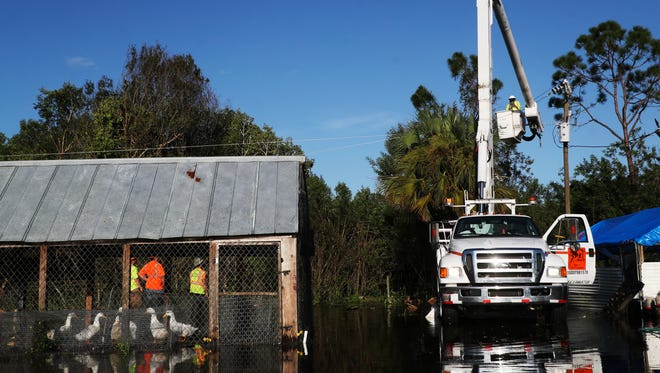 A crew contracted by LCEC restores power to a North Fort Myers residence on Tuesday.