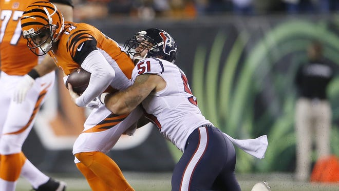 Cincinnati Bengals quarterback Andy Dalton (14) is tackled for a loss by Houston Texans outside linebacker John Simon (51) in the fourth quarter during the Week 10 NFL football game between the Houston Texans and the Cincinnati Bengals, Monday, Nov. 16, 2015, at Paul Brown Stadium in Cincinnati.