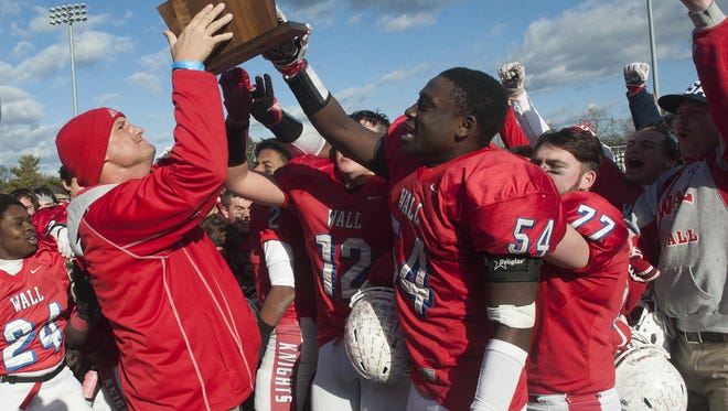 Dan Curcione (left) and Darryin Valme (54) hoist the trophy after winning an NJSIAA sectional championship game over Delsea in December 2016.