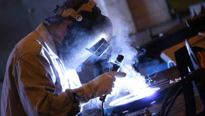 Arc welder at work at his workbench at Mayville Engineering.