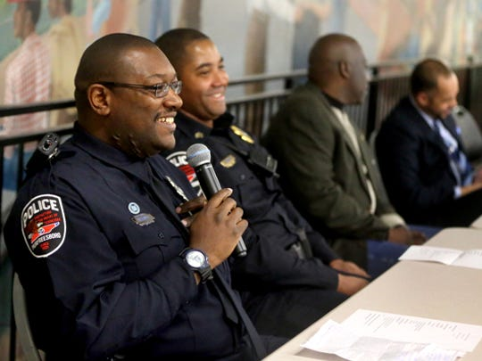 """Murfreesboro Police Officer Christopher Williams, foreground, answers questions and concerns from the community about relations between the community and law enforcement during the 2015 """"Hands Up! Don't Shoot Teen Summit"""" panel discussion at Patterson Park Community Center. Seated beside him are MPD Sgt. Reco Hathaway, Riverdale teacher and coach Rickey Field and federal public defender Dumaka Shabazz."""