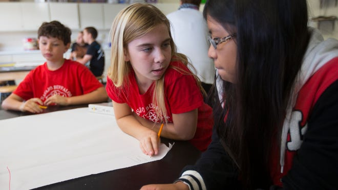 The Scottsdale district is using its newly passed override in an ad campaign to lure back students who have left the district. Aly Pickett, left, talks with Giselle Hernandez about their garden project at Navajo Elementary School in Scottsdale.