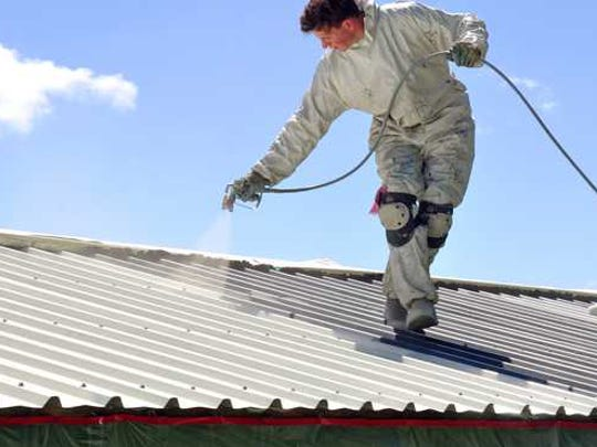 Man spraying a white roof.