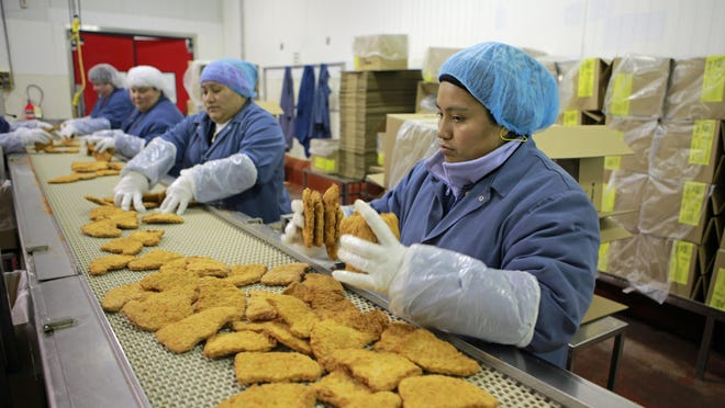 AdvancePierre Foods workers sort through breaded pork patties on the assembly line at the company's West Chester manufacturing plant.