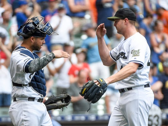 Catcher Manny Pina greets closer Corey Knebel after the Brewers closed out the Mets on Sunday at Miller Park.