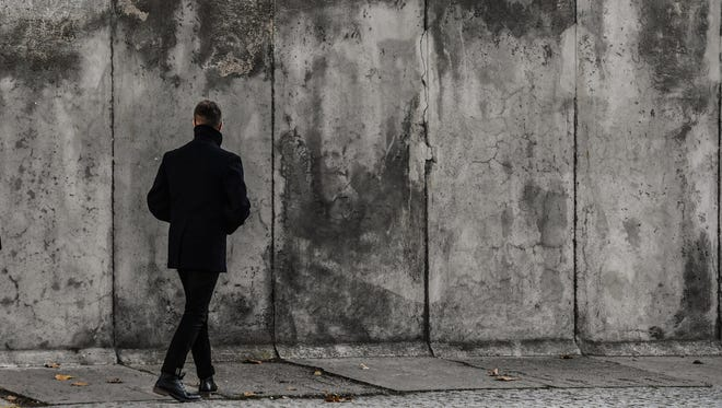 A man walks along a part of the Berlin Wall, at the Berlin Wall memorial site in Berlin, Germany, Nov. 8, 2017. Nov. 9 marks a significant date in German history when both the Fall of the Berlin Wall as well as the 'Kristallnacht' or 'Reichskristallnacht' (lit.: Crystal Night, or Night of Broken Glass) are commemorated.