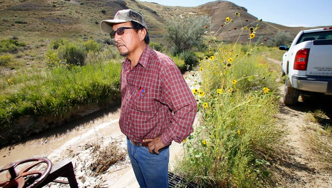 Shiprock Irrigation Supervisor Marlin Saggboy, watches water flow past an irrigation gate along the Fruitland Irrigation canal in Upper Fruitland, N.M. in this August 2015 file photo.