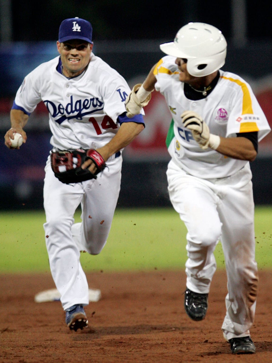 Los Angeles Dodgers' second baseman Jamey Carroll, left runs after Taiwan all-star S.W. Wang, during the first of three exhibition games against Taiwan all-star players in Taipei, Taiwan, Friday, March 12, 2010. Taiwan beat the Dodgers 5 to 2. (AP Photo/Wally Santana)