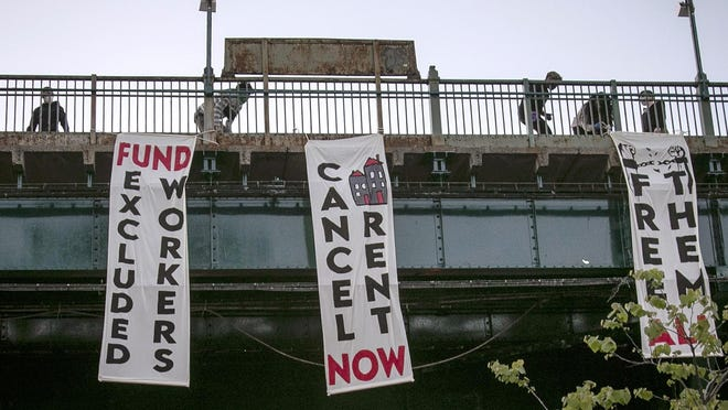 In this May 21, 2020, photo, people from a support organization for immigrant and working class communities unfold banners, including one advocating rent cancellation, on a subway platform in the Queens borough of New York during a vigil memorializing people who died from coronavirus.