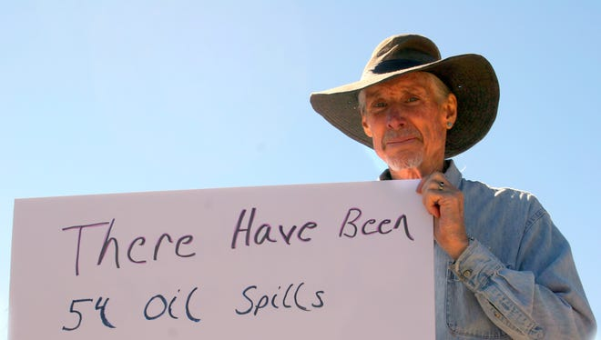 Grant County resident Ian Bailey holds a sign at a recent anti-pipeline protest.
