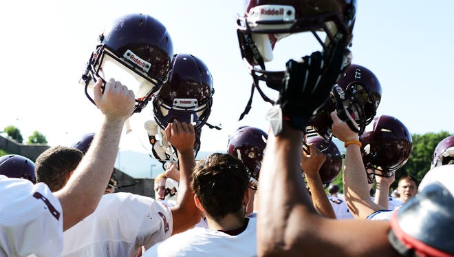 Owen football players raise their helmets at the conclusion of a recent practice.