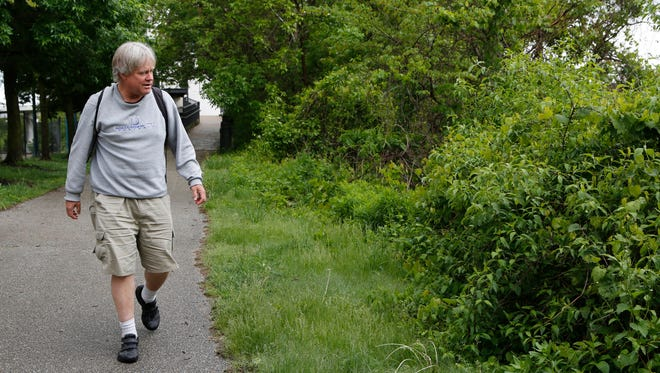 Nick Harby forages for edible plants Friday along the Wabash Heritage Trail in Lafayette.