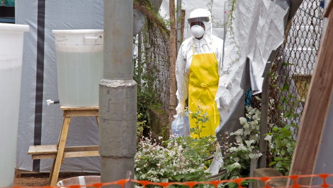 A healthcare worker walking near a Ebola isolation unit wearing protective gear against the virus at Kenema Government Hospital in Kenema, Sierra Leone.