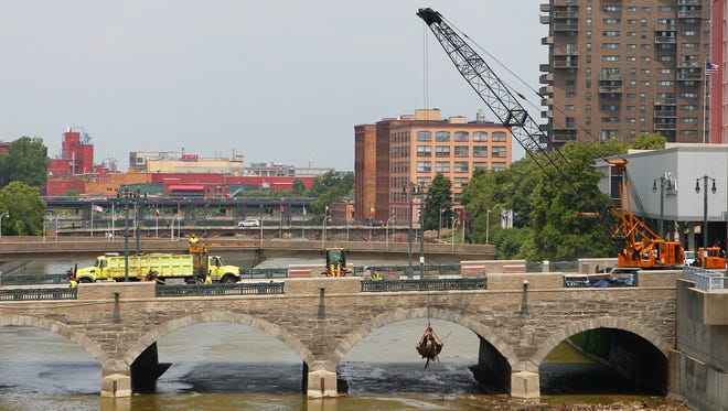 The river cleanup is an annual chore for city workers. Here crews clear logs and debris last June from the Genesee river under and around the Main Street bridge.