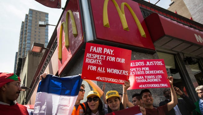 Protesters lobby for higher wages for fast food workers and urge fast food workers from around the globe to join their campaign outside a McDonalds on May 7.