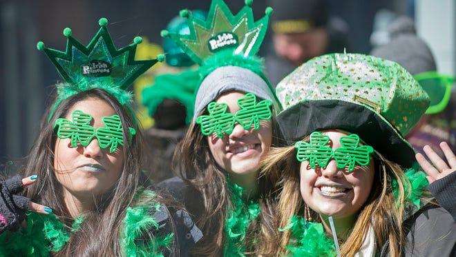 Spectators smile as the watch the annual St. Patrick's Day parade in Montreal, Sunday.