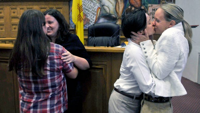From left, Heidi Macdonald and her spouse Monica Ewing, from Santa Fe, and Krista Turner and her spouse Lisa Hunsicker, from Albuquerque, embrace after they were married along with other same-sex couples in the Santa Fe County Commission Chambers, Aug. 23, 2013.