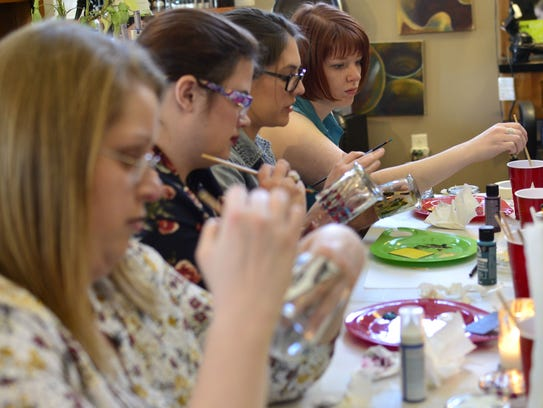 Community members participate in a candle-making fundraiser