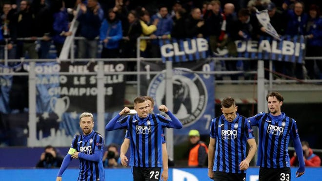 """From Feb. 19, 2020, Atalanta's Josip Ilicic, second left, celebrates with teammates after scoring his side's second goal during the Champions League round of 16, first leg, soccer match between Atalanta and Valencia at the San Siro stadium in Milan, Italy. It was the biggest soccer game in Atalanta's history and a third of Bergamo's population made the short trip to Milan's famed San Siro Stadium to witness it. Nearly 2,500 fans of visiting Spanish club Valencia also traveled to the Champions League match. More than a month later, experts are pointing to the Feb. 19 game as one of the biggest reasons why Bergamo has become one of the epicenters of the coronavirus pandemic — a """"biological bomb"""" was the way one respiratory specialist put it — and why 35% of Valencia's team became infected. The new coronavirus causes mild or moderate symptoms for most people, but for some, especially older adults and people with existing health problems, it can cause more severe illness or death."""