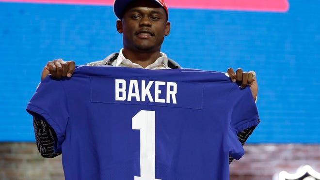 From April 25, 2019, Georgia defensive back DeAndre Baker poses with his new jersey after the New York Giants selected him in the first round at the NFL football draft in Nashville, Tenn. Police in South Florida are trying to find Giants cornerback Baker and Seattle Seahawks cornerback Quinton Dunbar after multiple witnesses accused them of an armed robbery at a party. Miramar police issued arrest warrants for both men Thursday, May 14, 2020.