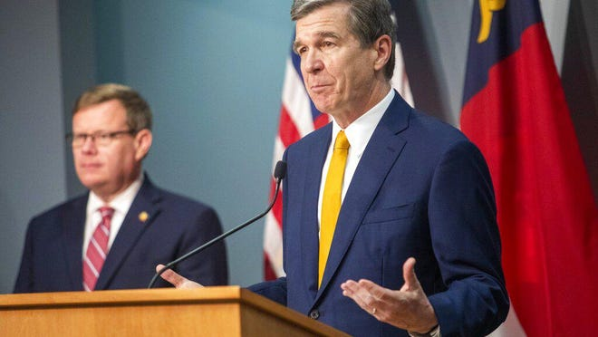 FILE - Gov. Roy Cooper speaks as House Speaker Tim Moore looks on during a briefing on North Carolina's coronavirus pandemic response Monday at the N.C. Emergency Operations Center in Raleigh.