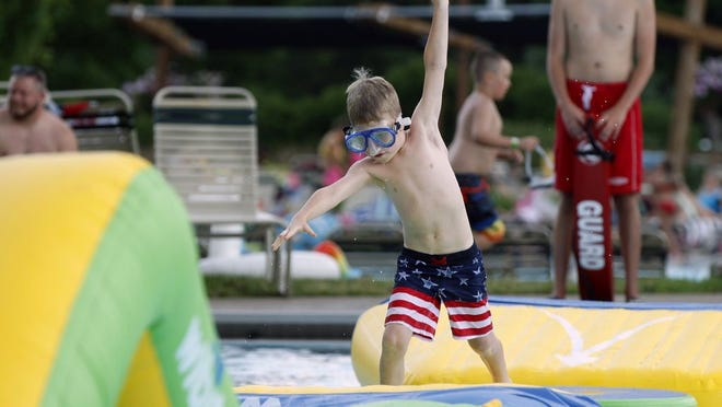 Benson Leavitt, 7, of New Albany, navigates his way across the WIBIT inflatable obstacle course June 19, 2019, at the Highlands Park Aquatic Center in Westerville.