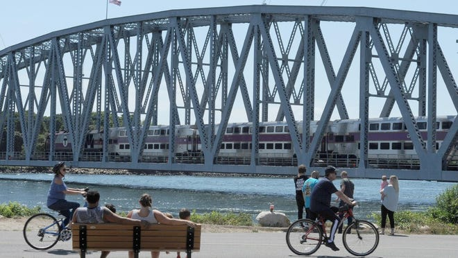 The CapeFlyer weekend commuter train from Boston to Hyannis draws a crowd as it crosses the Cape Cod Canal at Buzzards Bay Park.