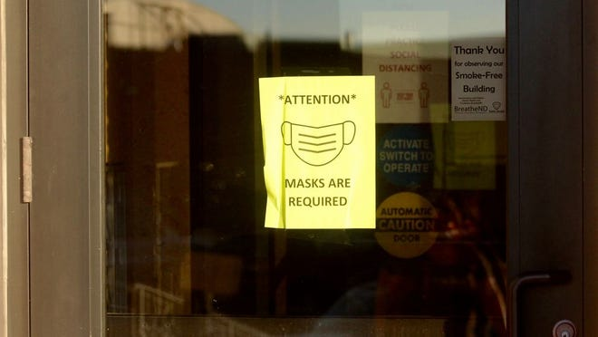 A sign requiring patrons to wear a mask inside hangs at the door of the Memorial Building in Devils Lake.