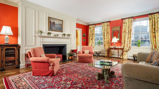 The living room welcomes you with two 8-over-8 sash windows that fill the space with sunny southeastern exposure and a view so high in the sky that it takes in the John Hancock Tower and the Old South Church spire. A paneled mantel, chair-railed wainscoting, streaky red-orange wallcovering and a diagonal parquet floor distinguish the living room.
