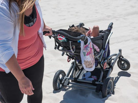 Erica Cirillo, Toms River, pulls her disabled child Leigha,  7, (in carriage) through the sand at the beach at F Street in Seaside Park. Jessica Krill (not pictured) of Toms River is on a crusade to make beaches more accessible for disabled people.