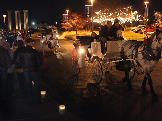 Paul Cross drives a horse-drawn carriage during the Enchanted Luminaria Walk at Minnetrista.