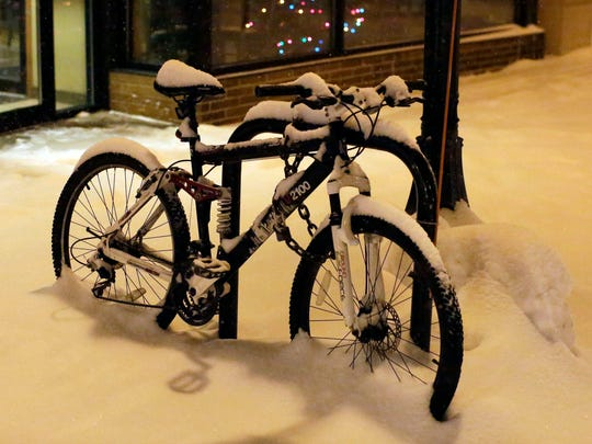 A bicycle, covered with snow, is locked on a bike rack