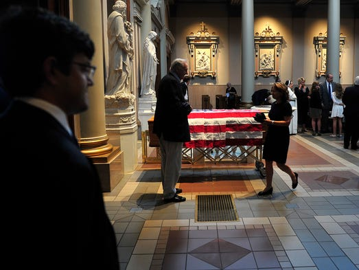 Visitors walk by the flag covered casket of George Barrett during the funeral at Cathedral of the Incarnation in Nashville, Tenn., Saturday, Aug. 30, 2014.