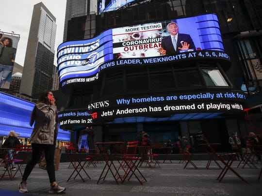 Pedestrians pass under a news ticker in Times Square, Wednesday, March 11, 2020, in New York, N.Y. The number of coronavirus cases in New York state jumped Sunday to more than 100, a spread that forced the suspension of classes at schools across the state, including a district that has a faculty member with a positive test and Columbia and Hofstra universities. For most people, the new coronavirus causes only mild or moderate symptoms. For some it can cause more severe illness. (AP Photo/John Minchillo)