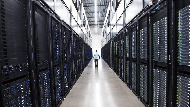 The senior site operations manager at the Apple Data Center in Mesa makes his way past dozens of servers, on Aug. 14, 2018.