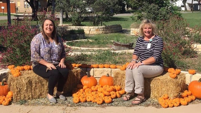 Jeanette Lancaster (left) and Kristi Owen are pictured in the pumpkin patch at Woodland Heights Elementary.