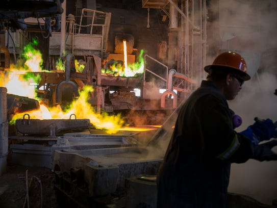 An Asarco worker prepares copper anode molds for casting