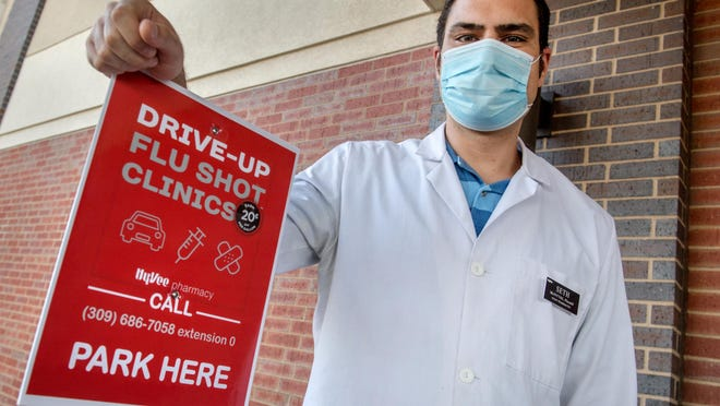 Seth McIntyre, a pharmacist with Hy-Vee, 4125 N. Sheridan Road in Peoria, stands next to a parking sign in the drive-thru area set aside for drive-up flu shots. The shots are being offered through Oct. 31 on Mondays from 7-11 a.m., Thursdays from 3-7 p.m. and Saturdays from 10 a.m. to 2 p.m. The pharmacist on duty will come out to your vehicle and administer the vaccine.