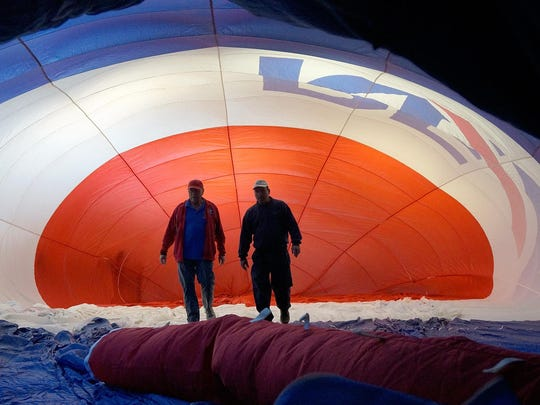 Pilots Marty Gauthier and Wes Dickerson make sure the balloon inflates properly as they ready it for more than 100 fourth- and fifth-graders at Farrand Elementary.