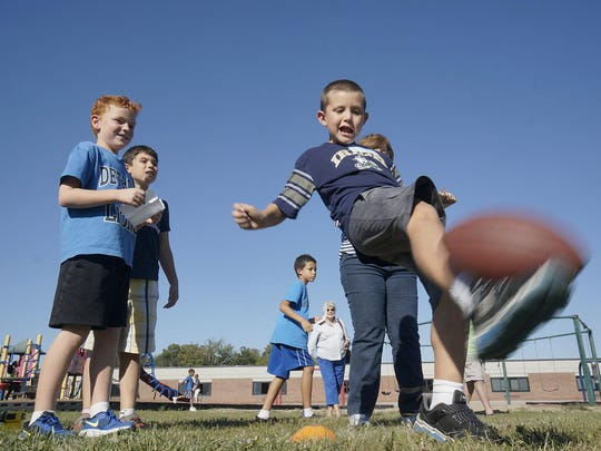 Aaron Proske and Bruno Delgado watch Brodi English punt the football during the Optimist Club-sponsored event.