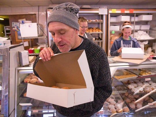 Customer Damian Bleecker takes a peek at his paczki.