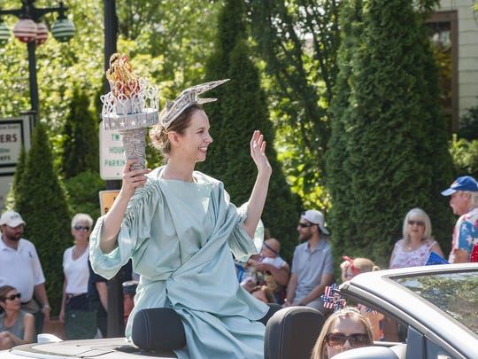Lady Liberty holds the torch high as the parade continues.